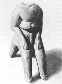 Πήλινο ειδώλιο καθιστού άντρα. Τα πόδια του ταυτίζονται με τα μπροστινά πόδια του καθίσματος. Νεολιθική περίοδος, Σέσκλο.