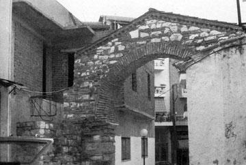 Άρτα, πυλώνας αγίας Θοδώρας. Έκδηλη η δυσαρμονία μεταξύ παλαιού και νέου κτίσματος.