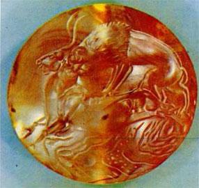 Λιοντάρι επιτίθεται σε ταύρο. Φακοειδής σφραγιδόλιθος από όνυχα. Θολωτός τάφος Μιδέας. 15ος αι. π.Χ. (Εθν. Αρχ. Μουσείο).