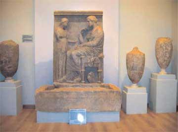 Μαρμάρινη στήλη και λήκυθοι σε αίθουσα του μουσείου. Ευρήματα από ταφικό μνημείο του 4ου αι. π.Χ. στην Παλλήνη.