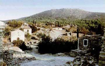 Το εκκλησάκι του Αϊ-Γιάννη στο χωριό Αγιάδες. Στο βάθος, το βουνό με την ακρόπολη, μέσα από το οποίο σκάφτηκε το όρυγμα.