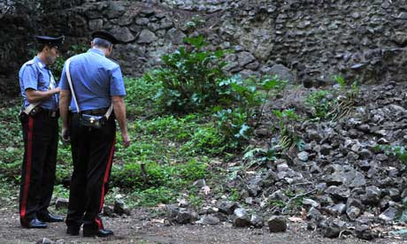 Italian police inspect the area where a Roman wall collapsed in Pompeii after heavy rain.