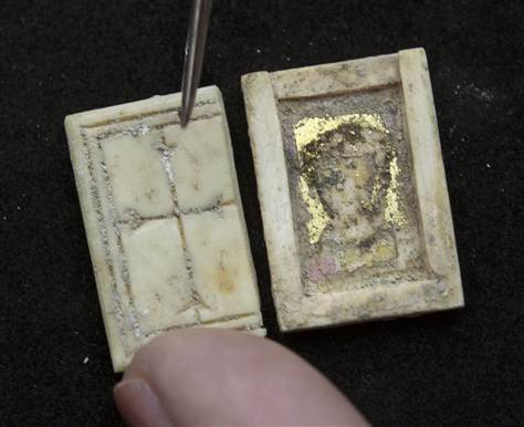 An Israel Antiquities Authority (IAA) restorer displays a Byzantine 2 by 1.5cm Christian icon box made of bone with a cross carved on the lid in Jerusalem.