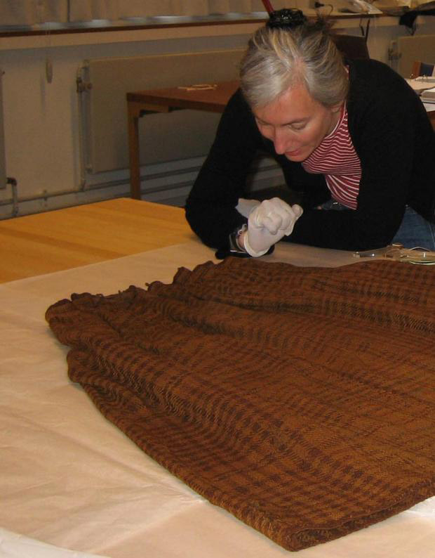 Archaeologist Ulla Mannering studying the skirt in the laboratory.