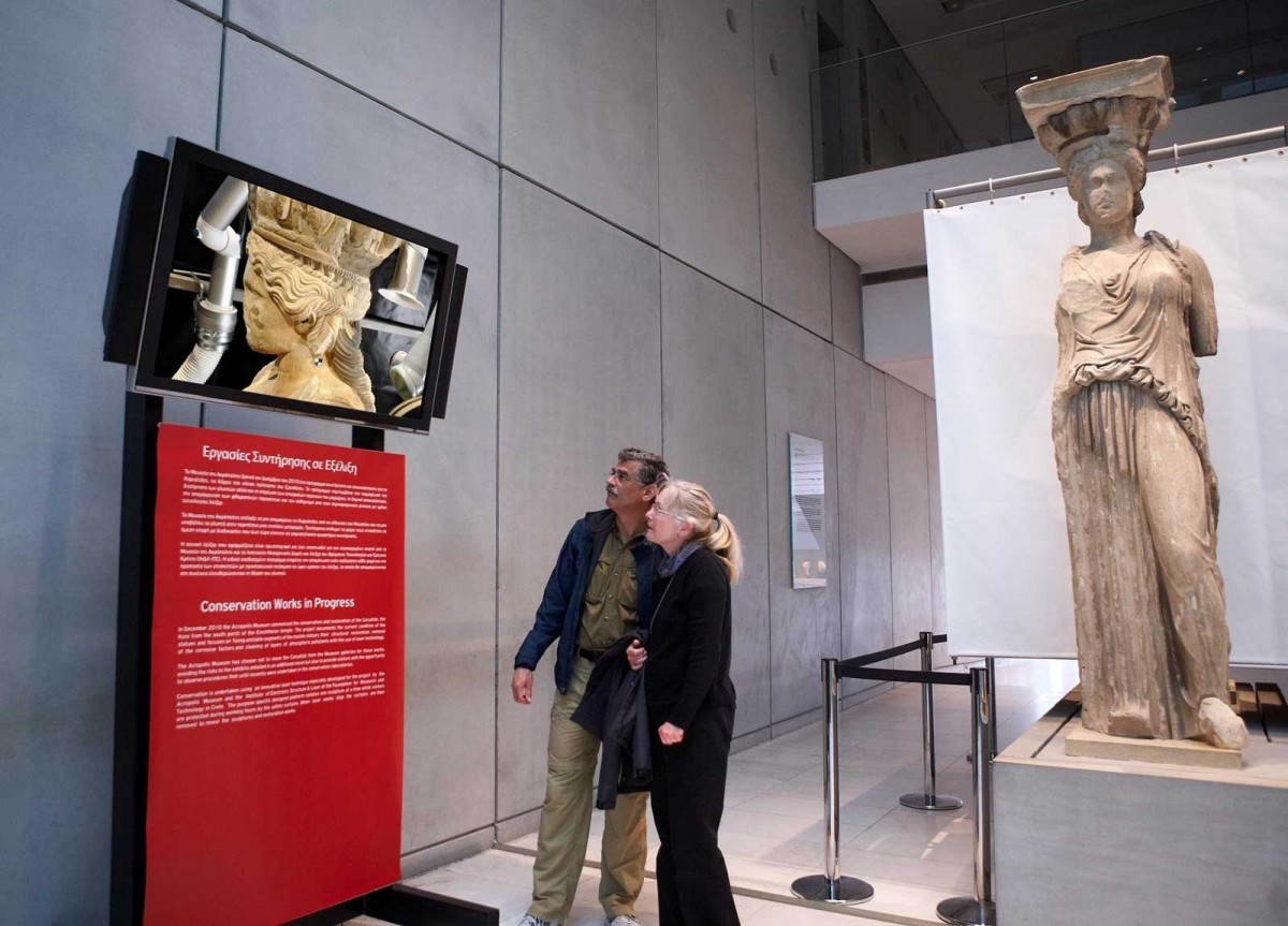 Visitors watching the video showing conservators do the delicate work of cleaning the Caryatids with advanced laser technology. © Acropolis Museum. Photo: Giorgos Vitsaropoulos.