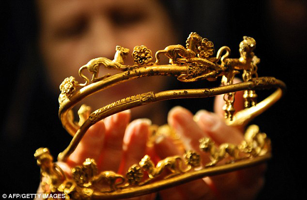 An archaeologist displays a gold tiara engraved with a lion's head and other animals found at the Bulgarian tomb.