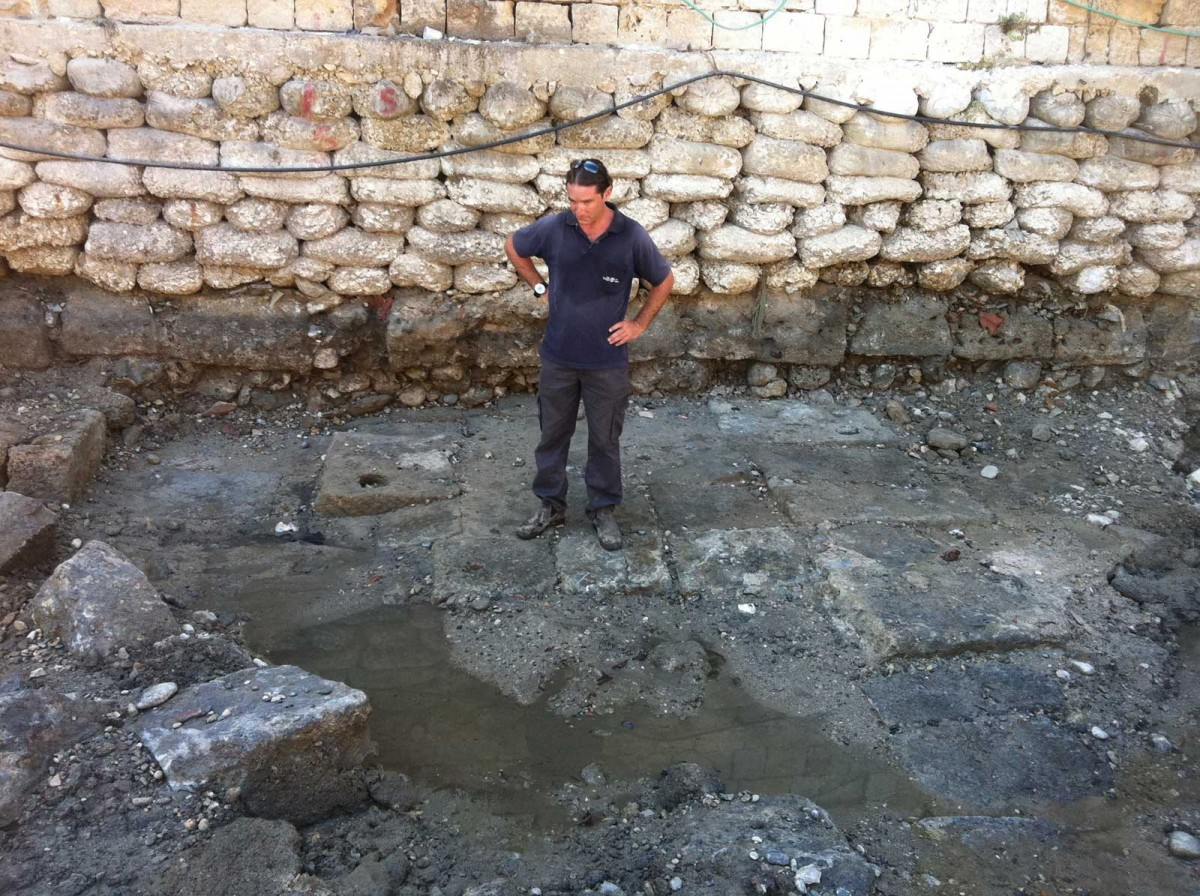 A member of the Marine Archaeology Unit of the Israel Antiquities Authority standing on the ancient quay that was exposed in Akko. (Credit: Israel Antiquities Authority)