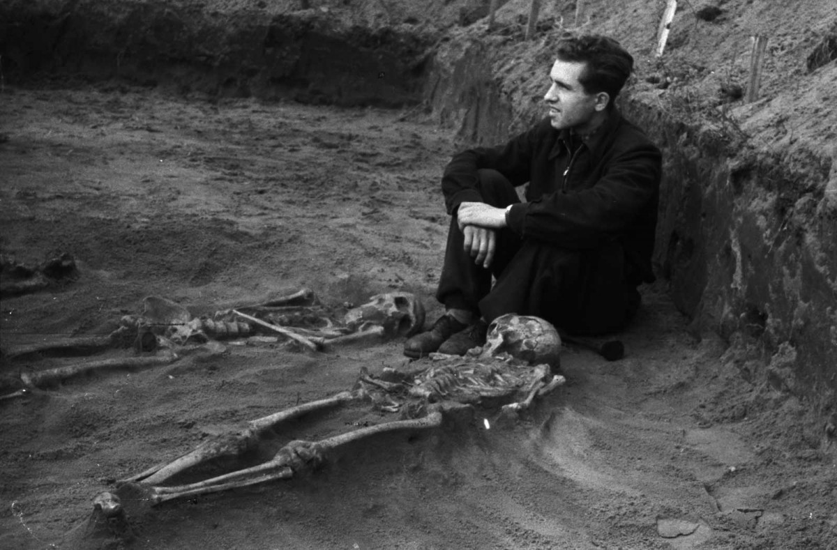 Man guarding recently uncovered human skeletons. © Europeana. Rights reserved.