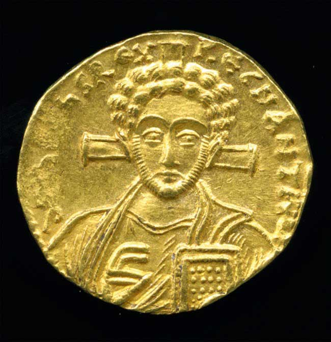 Gold solidus showing a bust of Jesus with a cross behind his head and holding a Bible. Minted in Constantinople (modern-day Istanbul, Turkey), AD 705–711.