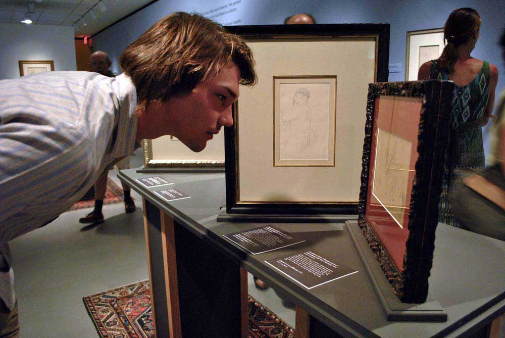 Visitor looks close at pages from Lautrec's sketchbook.