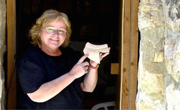 Dr. Eilat Mazar displays an alphabetically inscribed jar fragment found at Ofel, Jerusalem.