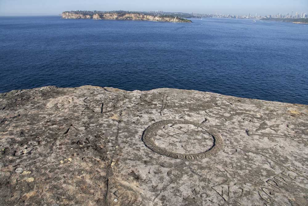 Inscriptions carved near the edge of a cliff at the North Head Quarantine Station with Sydney's skyline in the distance. Credit: copyright Ursula Frederick.