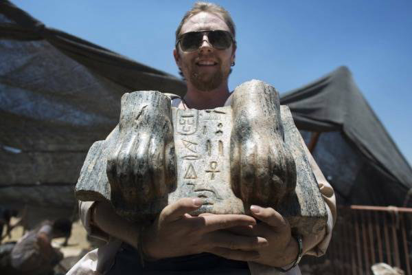 An archaeologist holding the Sphinx of Mycerinus found at Tel Hazor. Photo: AFP.