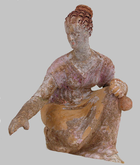Teracotta figurine of young female knucklebone player, early Hellenistic period (NM 12112). In her left hand she holds a knucklebone pouch (formiskos).