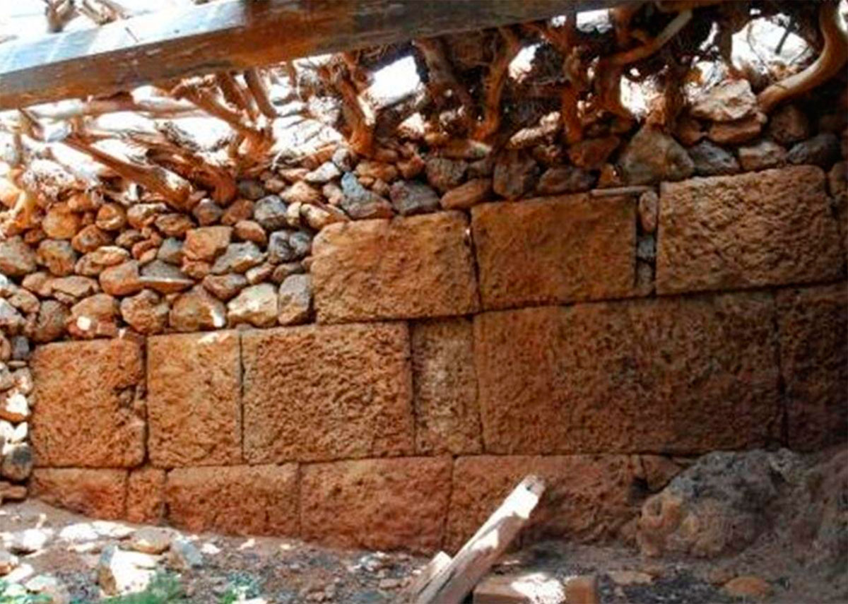 "Fig. 23. Part of the southern fortification wall of the ancient city, inside the houses of the settlement at ""Kastro"". It was strong enough to ensure the building of a later structure on top of it."