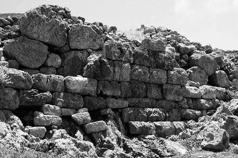 "Fig. 27. View of the wall of the Acropolis, towards the city. The polygonal ""rough"" construction was later covered with a pseudo-isodomic wall increasing thus the thickness of the wall at about 50-60 cm."