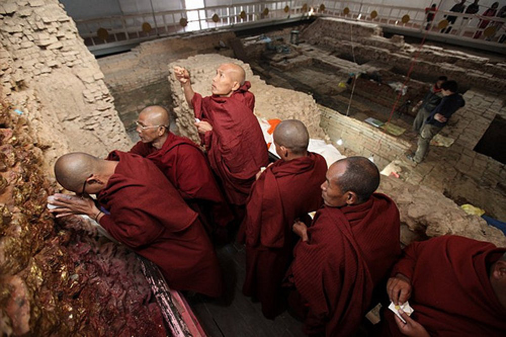 Pilgrims meditate at the wall below the nativity scene within the Maya Devi Temple at Lumbini, Nepal. The remains of the earliest temples at the site are in the background. Photo: Ira Block/National Geographic/National Geographic Buddha Birthplace.