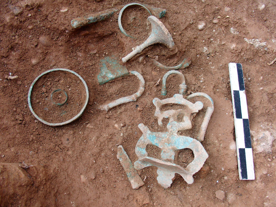 Fig. 3. Marmara: bronze objects in the naiskos' interior. A figurine of a winged figure (possibly part of a wooden vessel or tripod), door implements, handles and two small bowls/phialae can be seen.