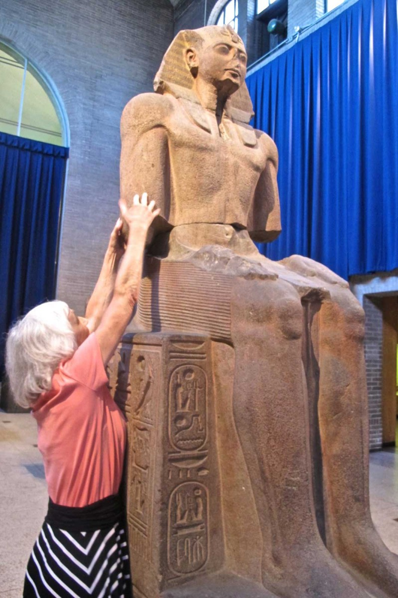 Carol Saylor, an artist who is deaf and blind, reaches to feel the scale of the throne of seated statue of Ramesses II during trial runs of an expanded