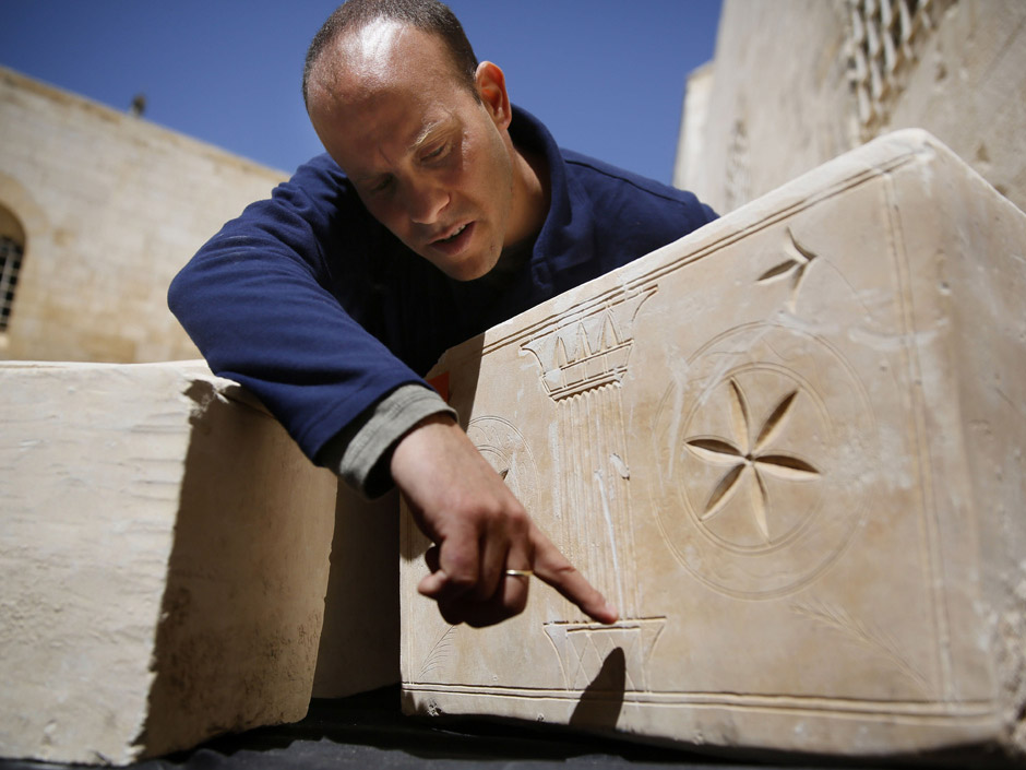 Archaeologist Dr. Eitan Klein explains motifs engraved in AD 1st c. ossuary found near Jerusalem. Photo: Gali Tibbon / AFP / Getty Images.