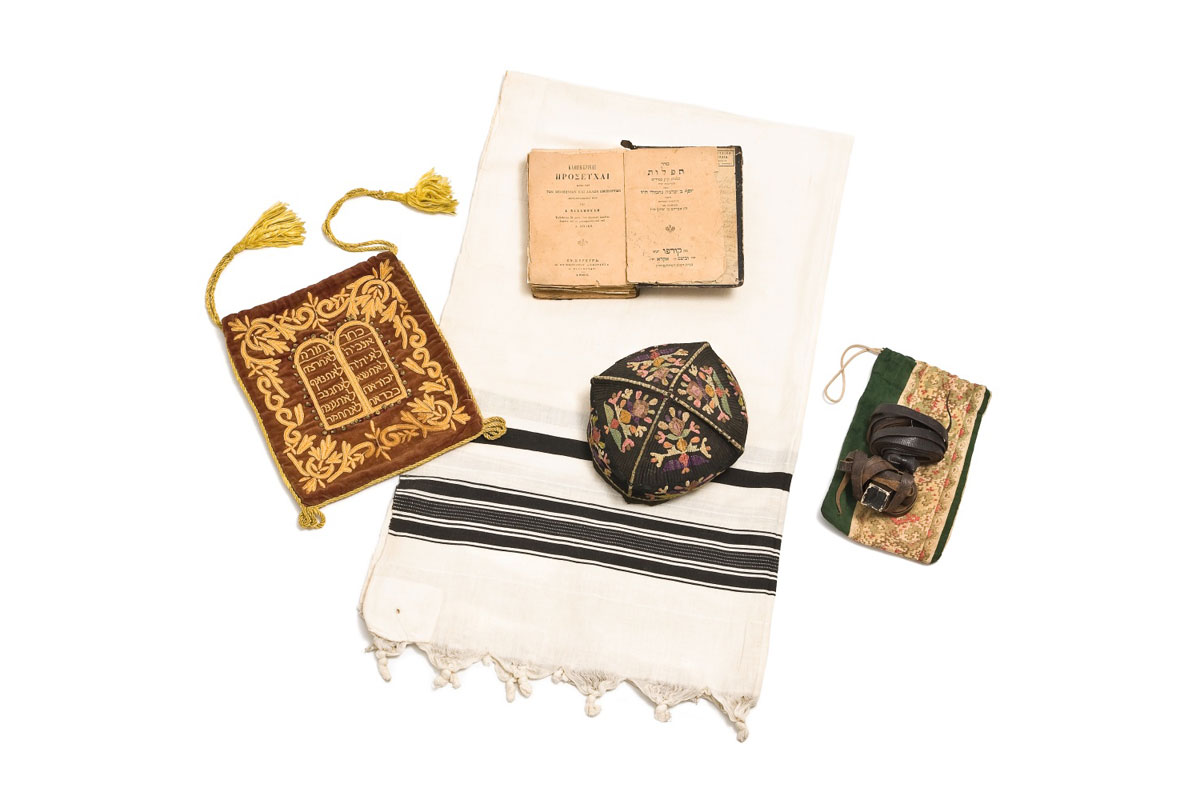 Fig. 3. The equipment for a Bar Mitzvah includes a Taleth (prayer shawl) with its case, a Tefilin (container), a Kipa (prayer cap) and a Sintour (prayerbook for daily prayers/ 19th-early 20th century (©The Jewish Museum of Greece, 2014).