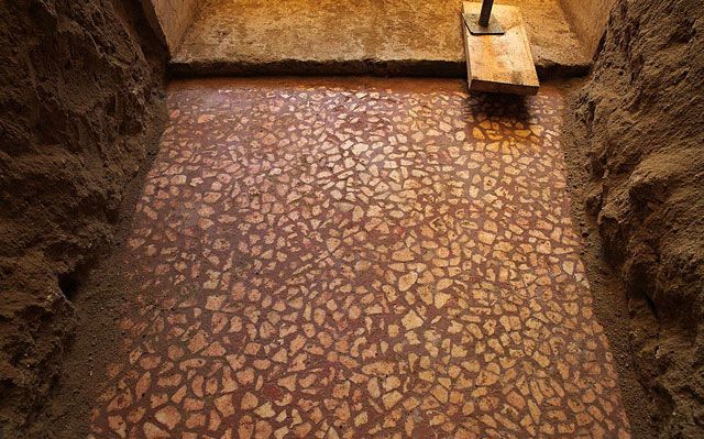 Amphipolis: Exceptionally well-preserved floor section made of irregular pieces of white marble on a red background.