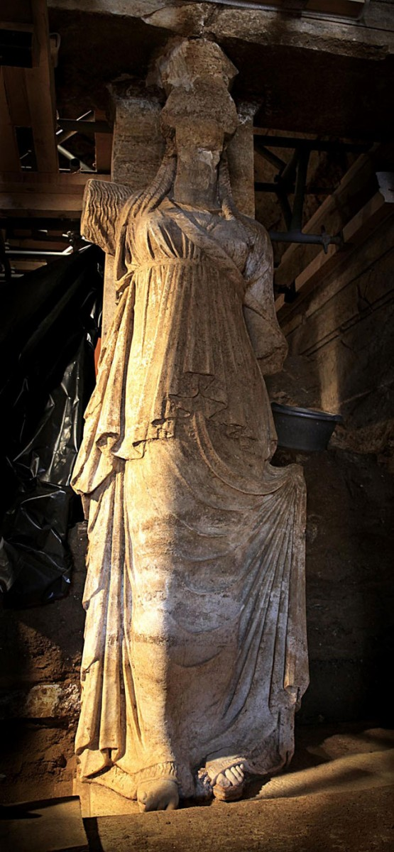 The Caryatids are wearing long chitons and a long fringed richly draped himation.