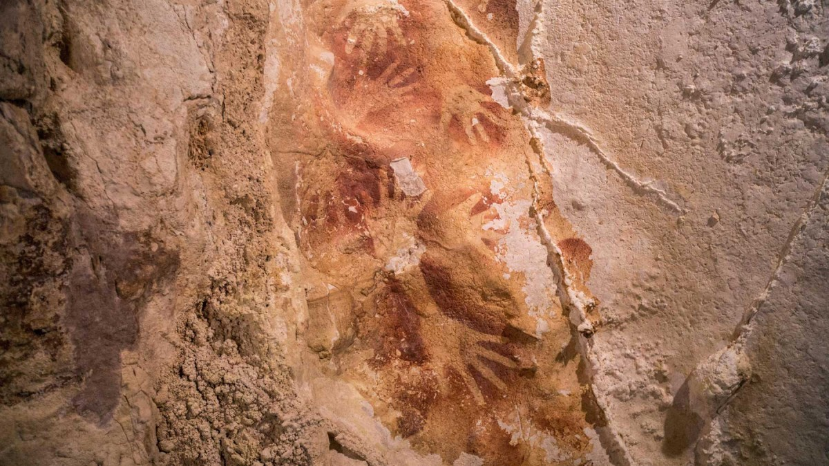 Australian and Indonesian scientists have dated layers of stalactite-like growths that have formed over coloured outlines of human hands.