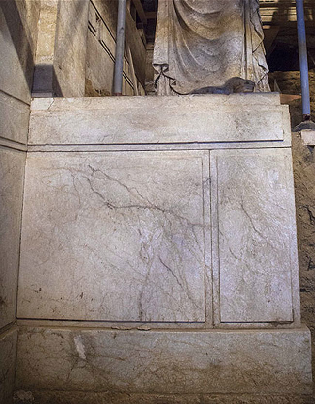 The decoration of the pedestals follows the marble revetment of the walls.