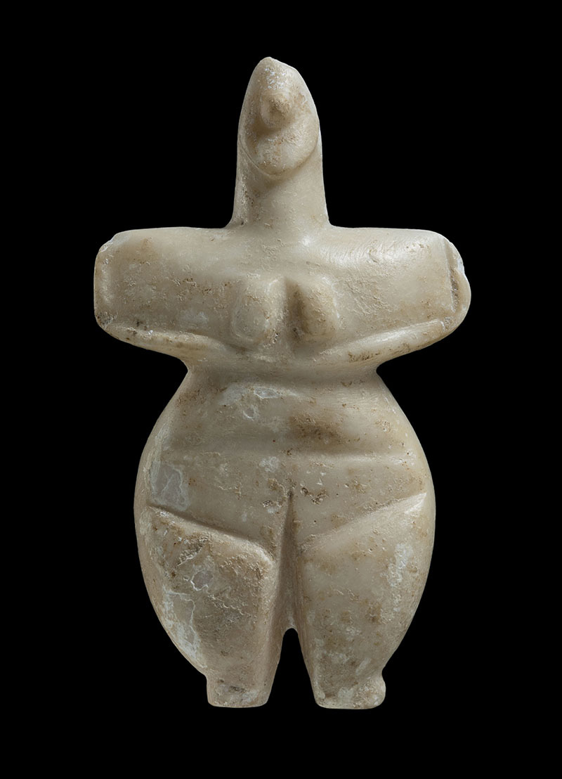 Female figurine. Late Neolithic I (5300-4800 BC). Off-white soft stone. H. 0.106 m, w. at shoulders 0.063 m.  Aigina, surface find in the Alones valley. Athens, National Archaeological Museum,  8772.