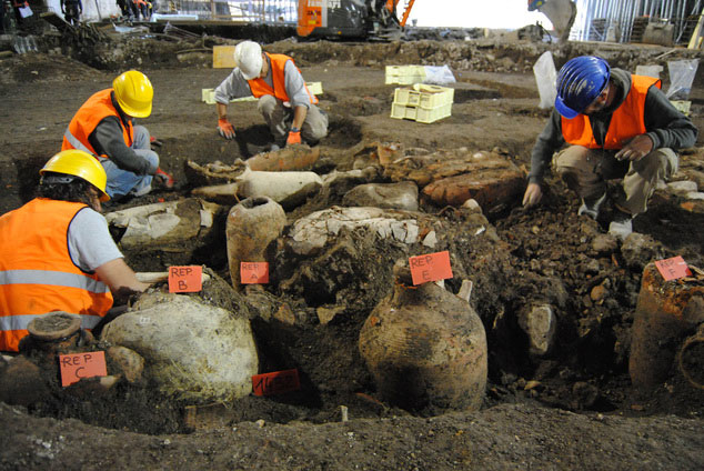 Archaeologists working next to unearthed amphorae at the site. Photo credit: Associated Press/Cooperative Archaeologia.