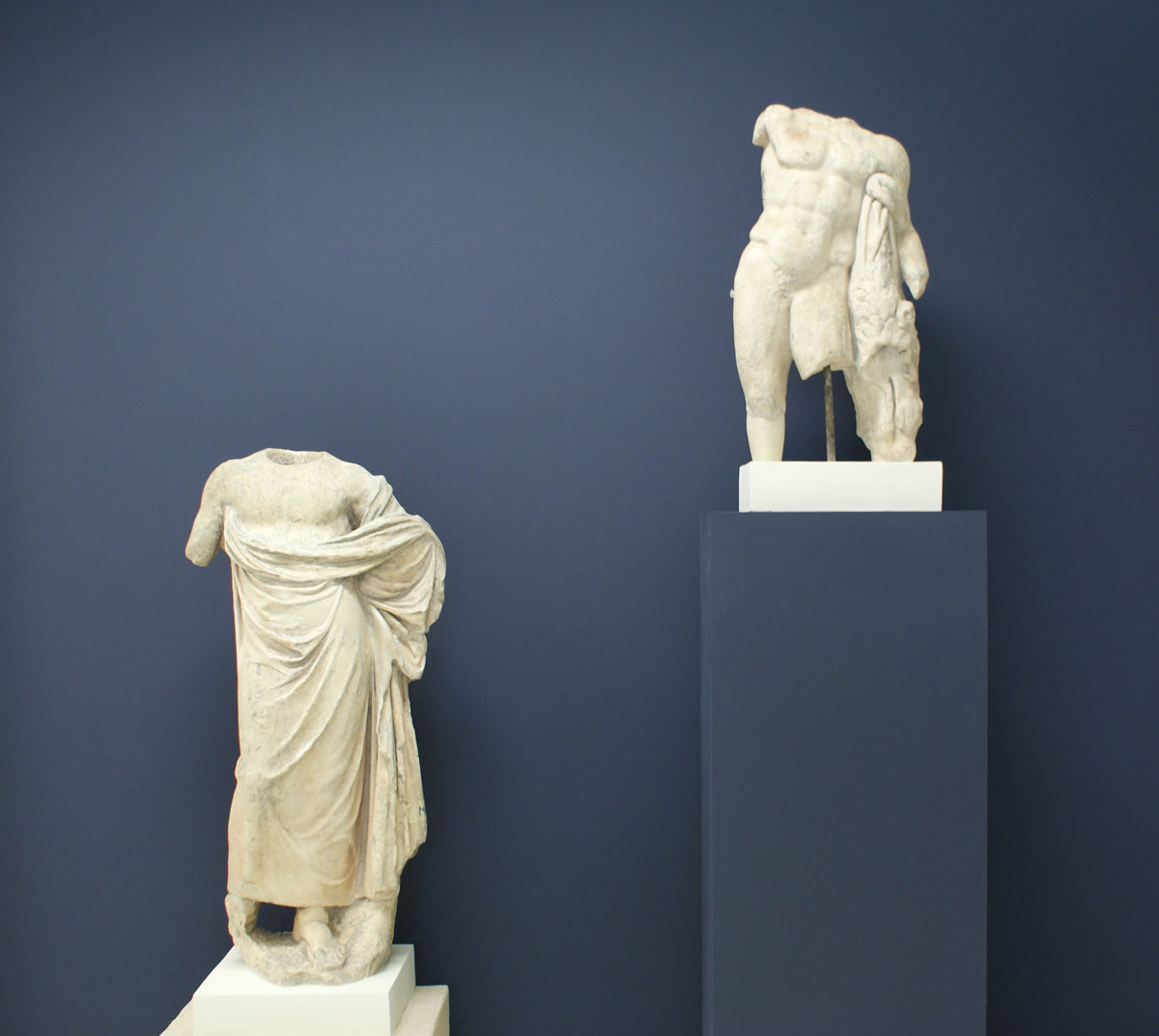 Left: Torso of statuette of Hercules. Possibly decoration of a trapezophoron (table support). Unknown provenance. AD 225-250. Right: Statuette of Asklipios. Of Pentelic marble. Provenance unknown. 1st c. BC.