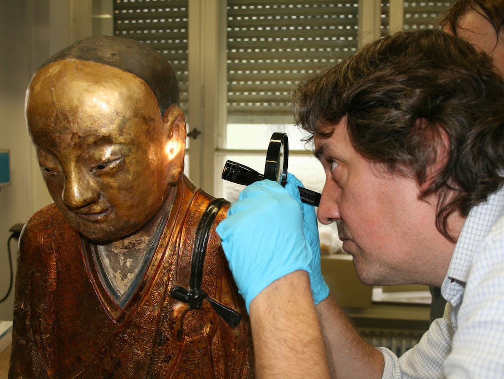 A gold-painted papier-mâché statue of the Buddha contained the mummified remains of an ancient Buddhist monk who lived during the 11th or 12th century. Here, a researcher inspects the statue. Credit: © Drents Museum.