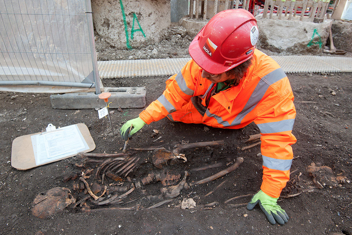 An archaeologist at Bedlam site while uncovering a bones. The works are due to finish in September. Photo Credit: MOLA.