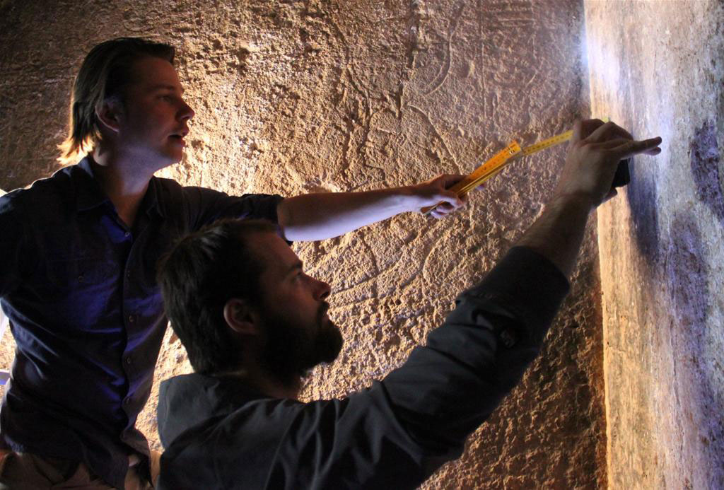 Wojciech Ejsmond, project leader, and Daniel Takacs, Egyptologist, analysing ornaments in the rock temple of Hathor. Photo Credit: P. Witkowski.