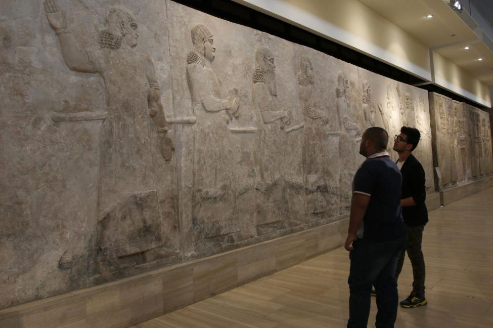 Visitors look at Assyrian mural sculptures from Khorsabad, at the Iraqi National Museum in Baghdad March 8, 2015. Photo Credit: Reuters / Khalid Al-Mousily.