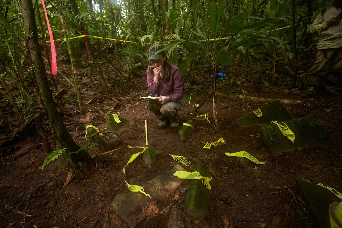 Anna Cohen, a University of Washington anthropology grad student, documents a cache of more than 50 artifacts discovered in the jungle. Following scientific protocol, no objects were removed from the site. The scientists hope to mount an expedition soon to further document and excavate the site before it can be found by looters. Photo Credti: Dave Yoder, National Geographic.