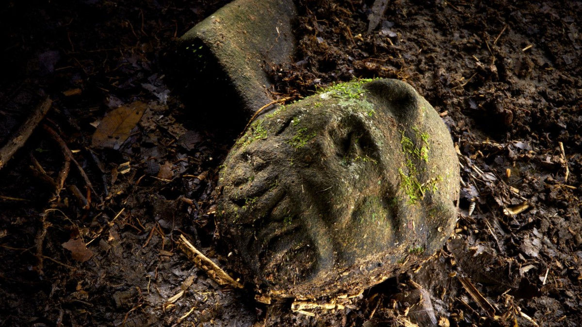 "A ""were-jaguar"" effigy, likely representing a combination of a human and spirit animal, is part of a still-buried ceremonial seat, or metate, one of many artifacts discovered in a cache in ruins deep in the Honduran jungle. Photo Credit: Dave Yoder, National Geographic."
