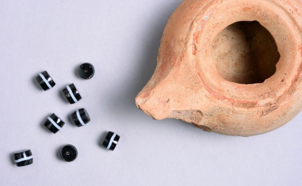 A clay lamp and beads from the Hellenistic period, found hidden in a cave in northern Israel, February 2015. Photo Credit: Clara Amit/Israel Antiquities Authority.