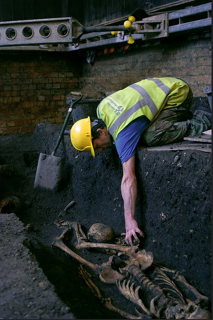 A member of the Cambridge Archaeological Unit excavates a 14th century skeleton.