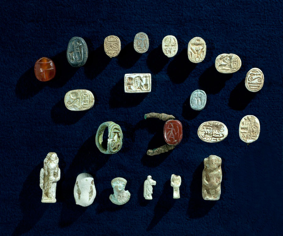 The collection of artifacts found in the cave includes faience amulets depicting Egyptian gods and scarab seals depicting Egyptian pharaohs. Photo Credit: Clara Amit / IAA.