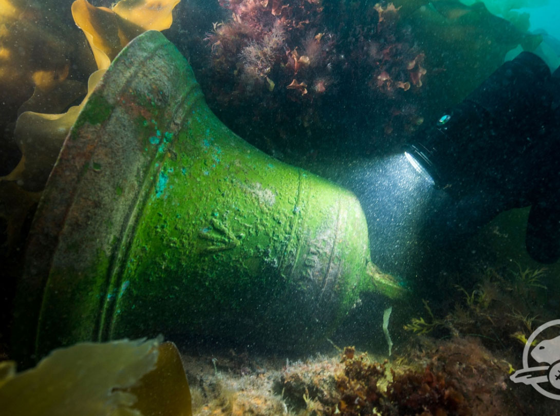 The ship's bell was found on the deck of the submerged ship next to the windlass. Photo Credit: Parks Canada.
