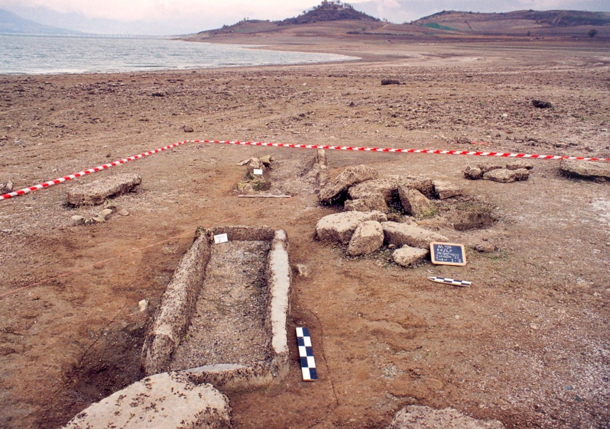 Fig. 3. Kriovrisi Kranidia, view of the eroded Late Bronze Age cemetery, within the Neolithic settlement. In the foreground a cist grave built with anthropomorphic stelae.