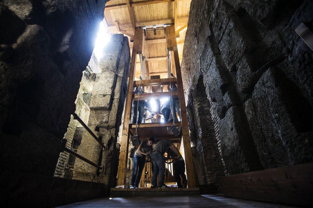 Men working on the replica of the elevator that took wild animals to the Roman Colosseum floor. (Credit: ANGELO CARCONI/epa/Corbis