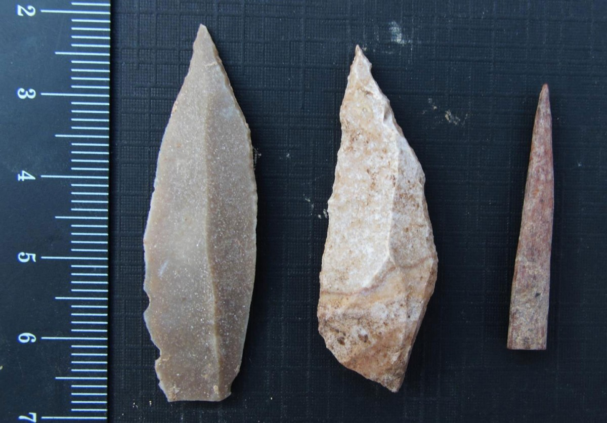 Two stone tool points were made using a prismatic blade technique (left and center), and a bone point or needle (right). Credit: Photo by Aaron Stutz, Emory University.