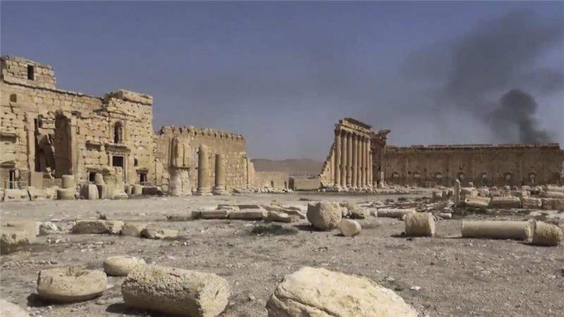 Smoke rises behind archaeological ruins in Palmyra, Syria. Photo Credit: AP.