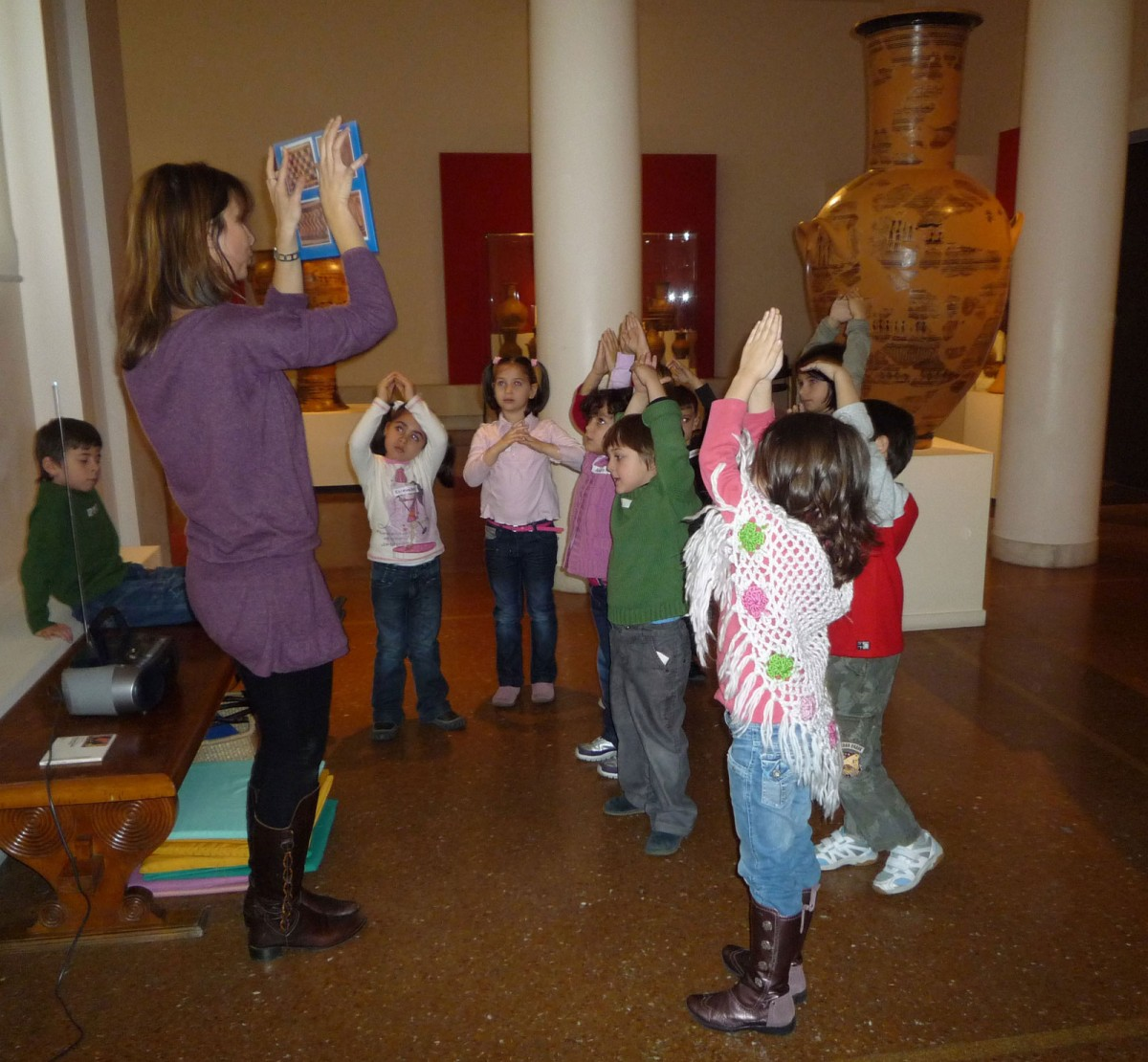 "Fig. 1. Children dance to the rhythm of ancient Greek music based on geometric motifs shown to them by the museum educator and a choreography based on pre-arranged movements (Educational programme ""The line trip in ancient times"" Photographic Archive, National Archaeological Museum)."
