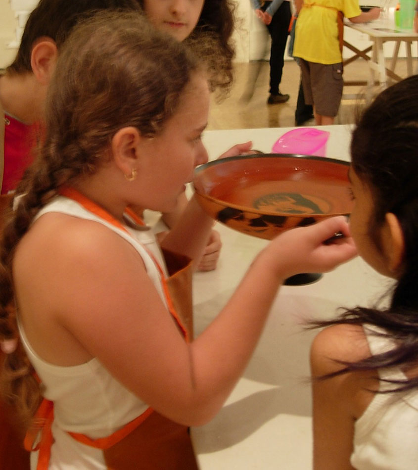 "Fig. 2. Children experience the use of the kylix with the help of a copy (Educational programme ""Rejoice and drink or else Cheers"", Photographic Archive, National Archaeological Museum)."