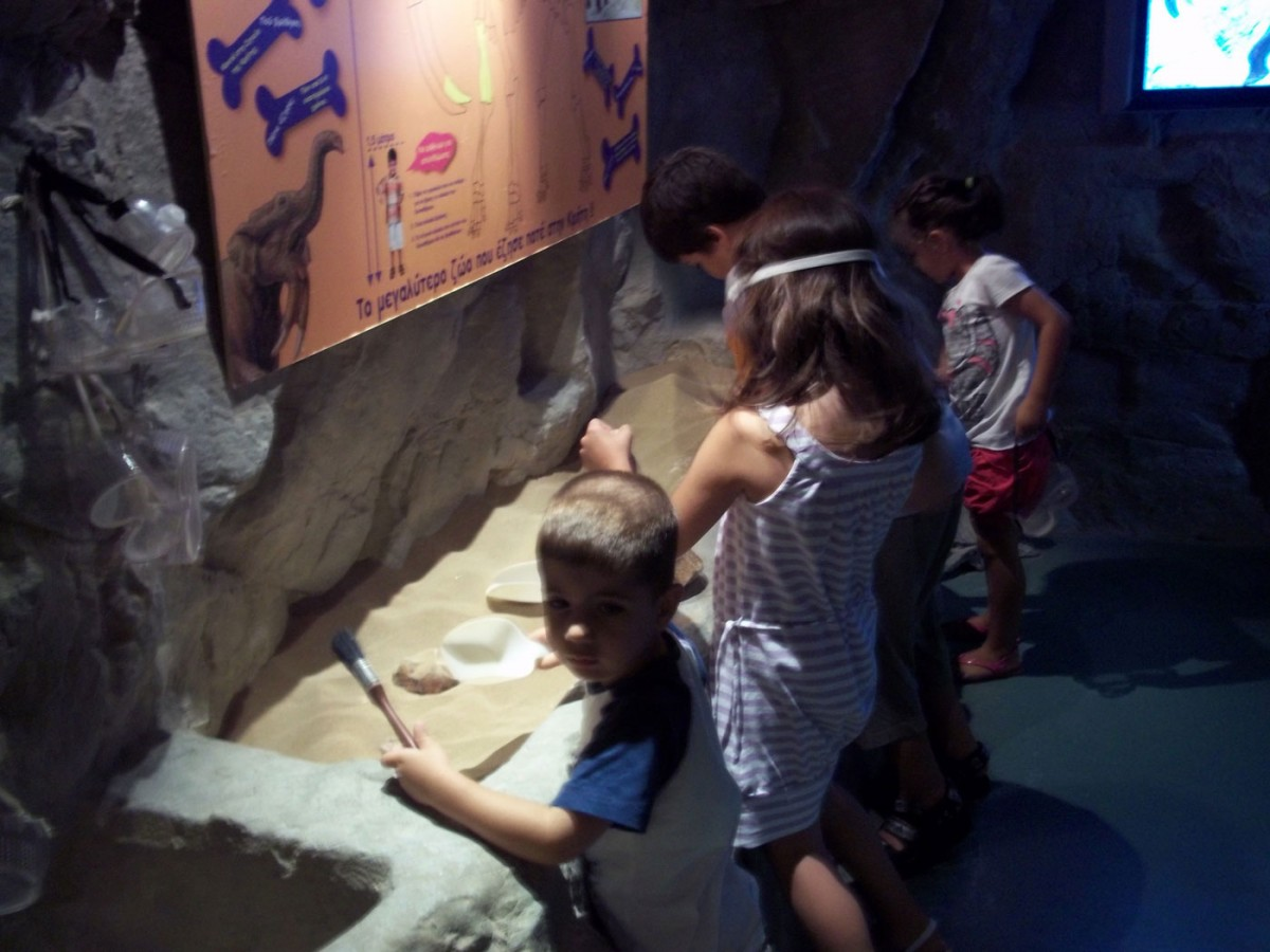"Fig. 7. Natural History Museum of Crete, children's wing ""Discovery Centre"". Excavating the bones of a deinothirio is an activity that can be companionable (Photographic archive of D. Kalessopoulou)."