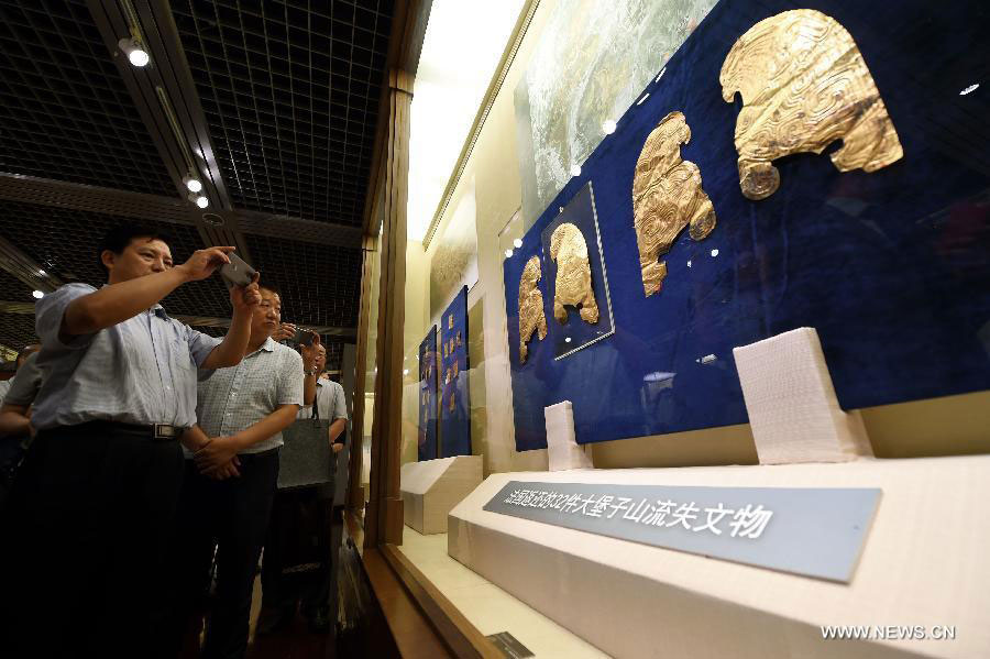 People visit the public exhibition of Chinese cultural relics returned by French  private collectors, at Gansu Provincial Museum in Lanzhou, capital of northwest  China's Gansu Province, July 20, 2015. Photo Credit: Xinhua/Fan Peishen.